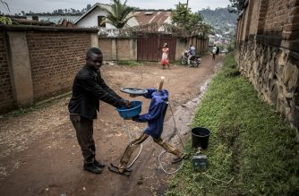 Electrical Engineer Germain Kasereka, demonstrates how a self made automatic hand washing robot works to assist in the fight against Ebola, on a street in Butembo on March 10, 2019. - The ebola virus is spread through touch, and the team believe that by the use of an automatic hand washing station, it will help stop people from touching the same tap handles before and after washing their hands. (Photo by JOHN WESSELS / AFP)