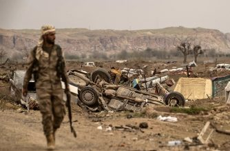 """EDITORS NOTE: Graphic content / A member of the Syrian Democratic Forces (SDF) walks past damaged vehicles on the side of a road in the village of Baghouz in Syria's eastern Deir Ezzor province near the Iraqi border on March 24, 2019, a day after the Islamic State (IS) group's """"caliphate"""" was declared defeated by the US-backed Kurdish-led Syrian Democratic Forces (SDF). (Photo by Delil souleiman / AFP)"""