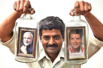 Artist Basavaraj poses with is bottle art creation of placing framed portraits of Indian Prime Minister Narendra Modi (L) and President of Indian National Congress Rahul Gandhi in narrow necked glass jars, in Bangalore on April 12, 2019. - India's gargantuan election, the biggest in history, kicked off on April 11 with Prime Minister Narendra Modi seeking a second term from the South Asian behemoth's 900 million voters. (Photo by MANJUNATH KIRAN / AFP)