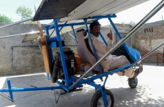 In this picture taken on April 8, 2019, Pakistani villager Muhammad Fayyaz poses for photographs as he sits in his small plane at his residence in Tabur village in central Punjab province. - The engine is from a roadcutter, the wings are burlap, the wheels are borrowed from a rickshaw: a Pakistani popcorn seller has caught the attention of the Air Force by building his own plane. (Photo by ARIF ALI / AFP) / To go with 'PAKISTAN-AVIATION-PLANE', FEATURE by Kaneez Fatima