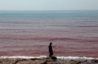 A woman walks along the beach on Hormuz Island in the Gulf Strait of Hormuz, off the Iranian port city of Bandar Abbas, on April 29, 2019. (Photo by ATTA KENARE / AFP)