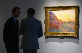 Sotheby's officials stand near one of Claude Monet's Meules during a media preview, for Sotheby's Impressionist & Modern Art and Contemporary Art auctions, May 3, 2019 in New York. (Photo by Don Emmert / AFP) / RESTRICTED TO EDITORIAL USE - MANDATORY MENTION OF THE ARTIST UPON PUBLICATION - TO ILLUSTRATE THE EVENT AS SPECIFIED IN THE CAPTION