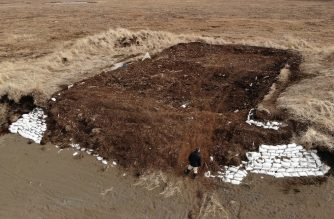 "Archaeologist Rick Knecht  (C bottom) at the excavation site beside the Bering Sea where he is searching for Yupik Eskimo artifacts, near the town of Quinhagak on the Yukon Delta in Alaska on April 13, 2019. - Knecht for the past 10 years has led a team racing to save as many items as possible at the excavation site located about three miles (4.8 kms) from Quinhagak and dubbed Nunalleq, which means Old Village in the Yupik language. (Photo by Mark RALSTON / AFP) / TO GO WITH AFP STORY by Jocelyne ZABLIT,  ""Alaska's thaw threatens prehistoric sites once frozen in time"""