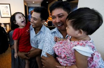Reuters journalists Wa Lone (R) and Kyaw Soe Oo celebrate with their children after being freed freed from Insein prison after a presidential amnesty in Yangon on May 7, 2019. - Two Reuters journalists who had been jailed for their reporting on the Rohingya crisis in Myanmar walked out of prison on May 7, freed in a presidential amnesty after a global campaign for their release. (Photo by ANN WANG / POOL / AFP)