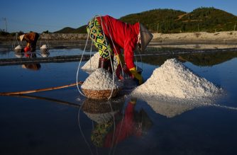 This photograph taken on April 22, 2019 shows workers harvesting salt in southern Vietnam's Hon Khoi salt fields. - The salt farmers of Hon Khoi rise before dawn as they have for generations, fanning out across shallow seawater pools to harvest the precious mineral, hoping for a better season than the last. (Photo by Manan VATSYAYANA / AFP) / TO GO WITH Vietnam-salt-industry-climate-economics, FEATURE by Jenny VAUGHAN and Tran Thi Minh Ha
