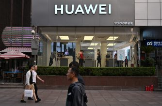 People walk past a Huawei store in Shanghai on May 10, 2019. (Photo by HECTOR RETAMAL / AFP)