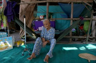 This photograph taken on April 21, 2019 shows 99-year-old Pham Thi Ca resting in a hammock in her makeshift shelter in Van Phong Bay. - Toothless and nearly blind, grandmother Pham Thi Ca refuses to leave her plot of land even after bulldozers demolished her house -- an extraordinary holdout against communist Vietnam's deepening addiction to coal. For power-hungry Vietnam coal is for now cheaper, more reliable and more familiar than renewables, which currently provide less than one percent of the country's power generation. (Photo by - / AFP) / TO GO WITH Vietnam-climate-energy-coal, FEATURE by Tran Thi Minh Ha with Jenny Vaughan