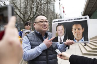 (FILES) This file picture taken on March 6, 2019 shows Louis Huang of Vancouver Freedom and Democracy for China holding photos of Canadians Michael Spavor and Michael Kovrig, who are being detained by China, outside British Columbia Supreme Court, in Vancouver, as Huawei Chief Financial Officer Meng Wanzhou appears in court. - China has formally arrested two Canadians who have been detained for months on national security grounds, Canada's The Globe and Mail newspaper reported on May 16, 2019 in a case that has inflamed tensions between Ottawa and Beijing. (Photo by JASON REDMOND / AFP)