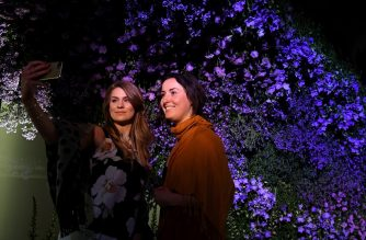Visitors take a selfie photograph in front of a display of flowers during a visit to the 2019 RHS Chelsea Flower Show in London on May 20, 2019. - The Chelsea flower show is held annually in the grounds of the Royal Hospital Chelsea. (Photo by Daniel LEAL-OLIVAS / AFP)