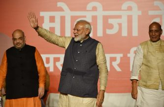 """India Prime Minister Narendra Modi (C) gestures to supporters next to Bharatiya Janta Party (BJP) president Amit Shah (L) and Minister of Home Affairs of India Rajnath Singh as they celebrate the victory in India's general election at the party headquarters in New Delhi on May 23, 2019. - Hindu nationalist Prime Minister Narendra Modi vowed an """"inclusive"""" future for all Indians on May 23 after a landslide election victory that crushed the Gandhi dynasty's comeback hopes once again. (Photo by PRAKASH SINGH / AFP)"""