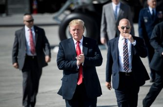 US President Donald Trump (C) gestures as he walks on the tarmac at Elmendorf Air Force Base in Anchorage, Alaska, during a refuel stop en route to Japan on May 24, 2019. - US President Donald Trump is travelling to Japan for a three-day official visit. (Photo by Brendan Smialowski / AFP)