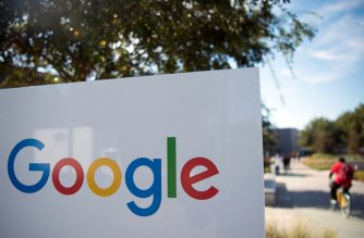A man rides a bike passed a Google sign and logo at the Googleplex in Menlo Park, California on November 4, 2016. (Photo by JOSH EDELSON / AFP)