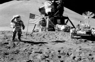 US cosmonaut James Irwin standing by the US flag waves on the moon during the Apollo 15 lunar mission on August 11, 1971. (Photo by - / NASA / AFP)