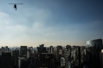 A helicopter overflies Sao Paulo, Brazil on June 23, 2017. - Airbus' subsidiary Voom gives an alternative for those willing to avoid Sao Paulo's heavy car traffic, offering a helicopter service similar to the car service offered by Uber. Sao Paulo counts one car every two inhabitants and during rush time there are between 330 and 576 km of traffic jams. (Photo by NELSON ALMEIDA / AFP)
