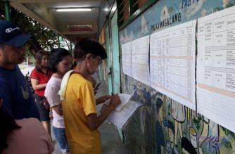 Voters look for their names at Manuel L Quezon L. Quezon Elementary School