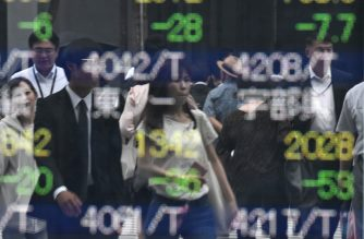 Pedestrians are reflected on an electronics stock indicator at the window of a securities company in Tokyo on June 3, 2019. (Photo by Toshifumi KITAMURA / AFP)