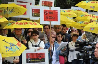 Demonstrators hold signs and yellow umbrellas as they gather in front of the Chinese Consulate in Vancouver, Canada, on June 9, 2019 to protest against a controversial extradition law proposed by Hong Kong's pro-Beijing government to ease extraditions to China. - An estimated 500 protesters gathered in front of the Chinese Consulate. (Photo by Don MacKinnon / AFP)