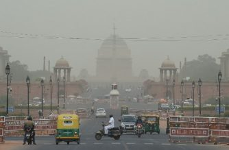 Vehicles pass by the Indian President house as dust covers the skyline in New Delhi on June 11, 2019. (Photo by Prakash SINGH / AFP)