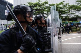 Police watch protesters during a rally against a controversial extradition law proposal outside the government headquarters in Hong Kong on June 12, 2019. - Hong Kong was facing growing international pressure over a controversial extradition bill that has prompted violent street protests. Police used rubber bullets and tear gas to break up crowds on June 12, after demonstrators -- angry over legislation they say would leave people vulnerable to China's politicised justice system -- blocked roads and brought the city to a standstill. (Photo by DALE DE LA REY / AFP)