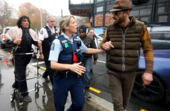 A member of the Muslim community speaks to a police officer after an argument with a man (not in picture) outside the Christchurch District Court on June 14, 2019, after Brenton Tarrant appeared in court via audio-visual link from a maximum-security prison in Auckland for a hearing. - Brenton Tarrant, the man accused of shooting dead 51 Muslim worshippers in the Christchurch mosque attacks pleaded not guilty to multiple murder and terrorism charges on June 14, 2019 and was committed to stand trial next year. (Photo by Sanka VIDANAGAMA / AFP)