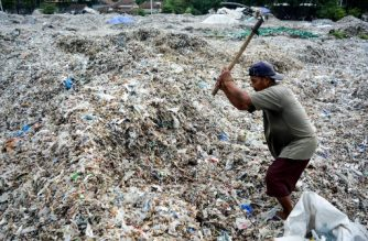 (File photo) In this picture taken on December 11, 2018 a man searches for plastic waste for resale at a dump in Mojokerto, East Java province. - Around 300 million tonnes of plastic are produced every year and end up in landfill or the seas, according to the Worldwide Fund for Nature (WWF). (Photo by STR / AFP)