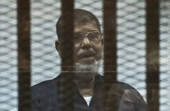 (FILES) In this file photo taken on June 16, 2015 Egypt's ousted Islamist president Mohamed Morsi stands behind the bars during his trial in Cairo. - Former Egyptian President Mohamed Morsi died on June 17, 2019 in a Cairo hospital after fainting in a court session, a judicial and security source said. (Photo by Khaled DESOUKI / AFP)