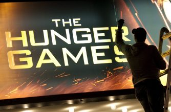 "(FILES) In this file photo taken on March 22, 2012 A worker swaps out the billboard marking the opening of  'The Hunger Games"" at the Ziegfeld Theatre in New York. - A new ""Hunger Games"" novel set decades before the original best-selling trilogy will be published next year, its publisher said on June 17, 2019, with plans for an accompanying film already under way. (Photo by Don EMMERT / AFP)"