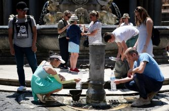 Tourists drink and fill their bottle from a public fountain to refresh themselves during an unusually early summer heatwave on June 24, 2019 in Rome. - Fans flew off store shelves and public fountains offered relief from the heat as temperatures soared in Europe on June 24, with officials urging vigilance ahead of even hotter conditions forecast later in the week. Meteorologists blamed a blast of torrid air from the Sahara for the unusually early summer heatwave, which could send thermometers up to 40 degrees Celsius (104 Fahrenheit) across large swathes of the continent. (Photo by Alberto PIZZOLI / AFP)