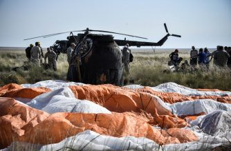 A search and rescue team works on the site of landing of the Soyuz MS-11 capsule carrying the International Space Station (ISS) crew of NASA astronaut Anne McClain, Russian cosmonaut Oleg Kononenko and David Saint-Jacques of the Canadian Space Agency, in a remote area outside the town of Dzhezkazgan (Zhezkazgan), Kazakhstan, on June 25, 2019. (Photo by Alexander NEMENOV / POOL / AFP)
