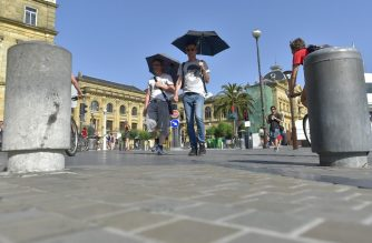 Two men hold umbrellas to protect themselves from the sun in the northern Spanish city of San Sebastian on June 26, 2019 at the start of a heatwave tipped to break records across Europe. - Experts say such heatwaves early in the summer are likely to be more frequent as the planet heats up -- a phenomenon that scientists have shown to be driven by human use of fossil fuels. (Photo by ANDER GILLENEA / AFP)