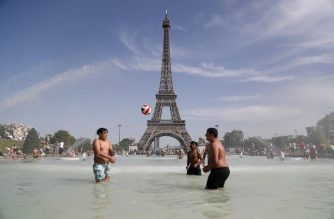 People play as they bathe in the Trocadero Fountain in front of the Eiffel Tower in Paris during a heatwave on June 28, 2019. - The temperature in France on June 28 surpassed 45 degrees Celsius (113 degrees Fahrenheit) for the first time as Europe wilted in a major heatwave, state weather forecaster Meteo-France said. (Photo by Zakaria ABDELKAFI / AFP)