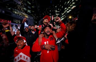 TORONTO, ON - JUNE 13: Toronto Raptors fans Subi Mahan cheers with his sons Kayan Mahan, on shoulders, and Kishan Mahan as fans gather to watch Game Six of the NBA Finals outside of Scotiabank Arena on June 13, 2019 in Toronto, Canada.   Cole Burston/Getty Images/AFP