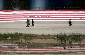 "Migrants walk past a large U.S. flag blanketing a portion of the border in protest to demand respect for migrants, as seen from Ciudad Juarez, Mexico, Friday, June 7, 2019. President Donald Trump announced late Friday that he had suspended plans to impose tariffs on Mexico, tweeting that the country ""has agreed to take strong measures"" to stem the flow of Central American migrants into the United States.  (AP Photo/Christian Torres)"