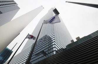 A Samsung flag (C) and South Korean national flag flutter outside the Samsung building in Seoul on January 31, 2019. - Samsung Electronics, the world's biggest smartphone and memory chip maker, reported a slump in fourth-quarter net profits on January 31, blaming a drop in demand for its key products. (Photo by Jung Yeon-je / AFP)