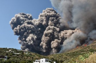 Smoke billows and flames propaqate accross the hillside neqr houses after the Stromboli volcano erupted on July 3, 2019 on the Stromboli island, north of Sicily. - A volcano on the Italian island of Stromboli erupted dramatically on July 3, killing a hiker and sending tourists fleeing into the sea. (Photo by Giovanni ISOLINO / AFP)