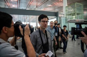 """Alek Sigley, an Australian student who was detained in North Korea, holds his passport and flight ticket as he heads for his departure at the Beijing International airport on July 4, 2019. - A 29-year-old Australian student detained in North Korea surfaced in Beijing on July 4, saying he felt """"great"""" after being released. Sigley was expected to travel to Japan, where his wife still lives. (Photo by NICOLAS ASFOURI / AFP)"""