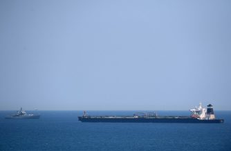 A British Royal Navy ship (L) patrols near supertanker Grace 1 suspected of carrying crude oil to Syria in violation of EU sanctions after it was detained off the coast of Gibraltar on July 4, 2019. - Authorities did not say where the oil came from but specialised shipping trade publication Lloyd's List said the Panamanian-flagged tanker was thought to be transporting crude from Iran. (Photo by JORGE GUERRERO / AFP)
