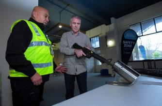 This photo taken on July 4, 2019 shows New Zealand police officers handling a gun example at a press preview ahead of a gun buyback scheme at the Trentham racecourse in Upper Hutt, near Wellington. - Dozens of New Zealanders handed in their firearms on July 13 as a gun buyback scheme went into operation aimed at ridding the country of semi-automatic weapons in the wake of the Christchurch mosque attacks. (Photo by DAVE LINTOTT / AFP)