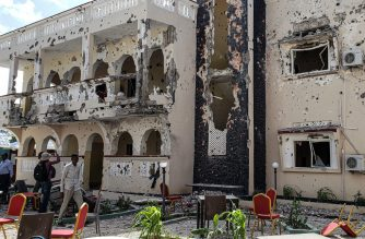 A man passes in front of the rubbles of the popular Medina hotel of Kismayo on July 13, 2019, a day after at least 26 people, including several foreigners, were killed and 56 injured in a suicide bomb and gun attack claimed by Al-Shabaab militants. - A suicide bomber rammed a vehicle loaded with explosives into the Medina hotel in the port town of Kismayo before several heavily armed gunmen forced their way inside, shooting as they went, authorities said. (Photo by STRINGER / AFP)