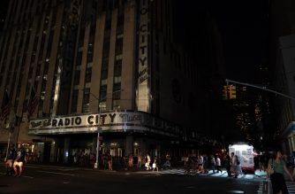 People walk past Radio City Music Hall in the dark during a major power outage affecting parts of New York City on July 13, 2019. - Subway stations plunged into darkness and the billboards of Times Square suddenly flicked off as New York's Manhattan was hit by a power outage on Saturday. About 42,000 customers lost electricity in the early evening, according to the Con Edison utility, which did not give a reason for the cut. (Photo by TIMOTHY A. CLARY / AFP)