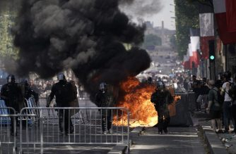 Members of the Gendarmerie stand in front of fences and a fire as protestors linked to the Yellow Vests (Gilets Jaunes) movement (unseen) take part in a demonstration on the side of the annual Bastille Day ceremony, on July 14, 2019, on the Champs-Elysees in Paris. (Photo by Kenzo TRIBOUILLARD / AFP)