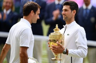 Serbia's Novak Djokovic (R) holds the winner's trophy and passes runner up Switzerland's Roger Federer (L) during the presentation at the end of the men's singles final on day thirteen of the 2019 Wimbledon Championships at The All England Lawn Tennis Club in Wimbledon, southwest London, on July 14, 2019. (Photo by Daniel LEAL-OLIVAS / AFP) / RESTRICTED TO EDITORIAL USE