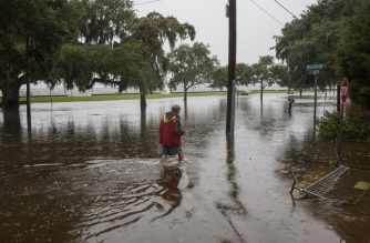 "A man wades through flood water after Tropical Storm Barry came ashore in Mandeville, Louisiana on July 14, 2019. - Tropical Storm Barry buffeted the US state of Louisiana, bringing more heavy rain and possible tornadoes to the region even as it weakened. After briefly becoming the first hurricane of the Atlantic season, Barry was downgraded to a tropical storm after making landfall on Saturday. It nevertheless moved inland with a serious punch. (Photo by Seth HERALD / AFP) / ""The erroneous mention[s] appearing in the metadata of this photo by Joseph Prezioso has been modified in AFP systems in the following manner: [Seth HERALD] instead of [Joseph Prezioso]. Please immediately remove the erroneous mention[s] from all your online services and delete it (them) from your servers. If you have been authorized by AFP to distribute it (them) to third parties, please ensure that the same actions are carried out by them. Failure to promptly comply with these instructions will entail liability on your part for any continued or post notification usage. Therefore we thank you very much for all your attention and prompt action. We are sorry for the inconvenience this notification may cause and remain at your disposal for any further information you may require."""