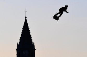 "Zapata CEO Franky Zapata flies a jet-powered hoverboard or ""Flyboard"" over the old harbour as part of  Bastille Day celebrations in Marseille on July 14, 2019. (Photo by Boris HORVAT / AFP)"