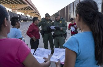 (FILES) In this file photo taken on May 16, 2019 US Customs and Border Protection agents check documents of a small group of migrants, who crossed the Rio Grande from Juarez, Mexico in El Paso, Texas. - The Trump administration moved on July 15, 2019 to block most migrants who cross the US southern border after passing through Mexico from seeking asylum.A new rule redefining asylum eligibility -- to take effect on Tuesday -- is the latest attempt to stem the flow of undocumented migrants into the country, and comes amid White House frustration at Congress's failure to change asylum laws. (Photo by Paul Ratje / AFP)