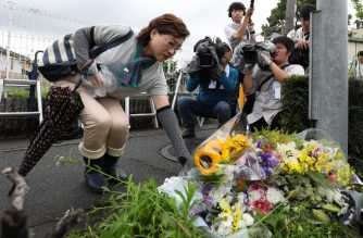 Residents place flowers for victims of a fire which hit the Kyoto Animation studio building the day before, killing 33 people, in Kyoto on July 19, 2019. - Japanese police are investigating a suspected arson that killed 33 people in one of the country's deadliest apparent crimes in decades, with the motive for the blaze still unclear. (Photo by JIJI PRESS / JIJI PRESS / AFP) / Japan OUT
