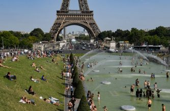 People cool off at the Trocadero Fountains next to the Eiffel Tower in Paris, on July 23, 2019 as a new heatwave hits Europe. - France and western Europe were bracing for a new record-breaking heatwave that is forcing the temporary shutdown of a French nuclear power station and will test competitors in the legendary Tour de France cycle race. Forecasters predicted new temperatures highs in a string of countries, including Belgium, Luxembourg and the Netherlands, where the mercury is set to reach 40 degrees Celsius (104 Fahrenheit) for the first time on July 23, 2019. (Photo by BERTRAND GUAY / AFP)