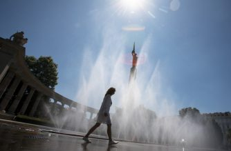 A woman walks past water sprayed from a pipe at the Schwarzenberg square in front of the monument of the Red Army in Vienna on July 25, 2019. - Weather forecasters predict new temperature highs across western Europe hit by another heatwave setting new temperature records. (Photo by ALEX HALADA / AFP)