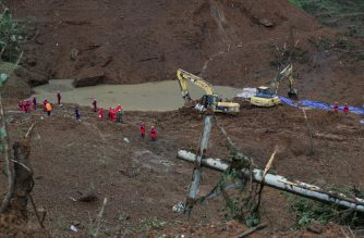 This photo taken on July 24, 2019 shows rescuers working at the site of a landslide in Liupanshui in China's southwestern Guizhou province. - The death toll in a landslide that buried a village in southwest China rose to 20 on July 26, with 25 people still missing three days after the disaster, state media said. (Photo by STR / AFP) / China OUT