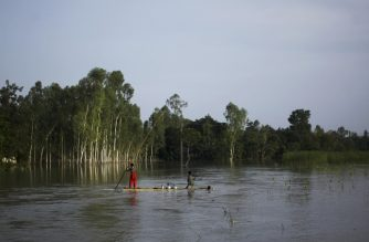 In this photograph taken on July 25, 2019, residents travel on a makeshift raft to collect drinking water in a flood afected area following monsoon rain in Kurigram district. - At least 104 people were killed in floods in Bangladesh as the low-lying delta country is reeling from one of the worst monsoons in years, officials said on July 26. Six villages went under water in northern Mymensingh district late Wednesday after flood water breached an embankment, displacing some 2,000 people, district administrator Mizanur Rahman told AFP. (Photo by STR / AFP)